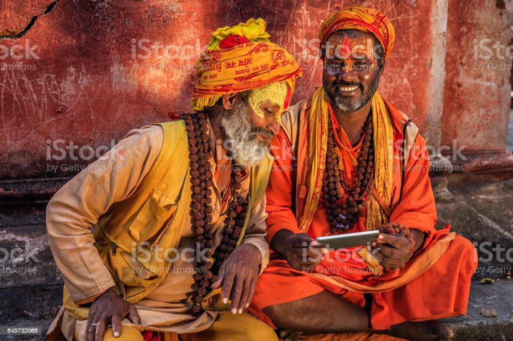 Sadhu - indian holymen using mobile phone stock photo
