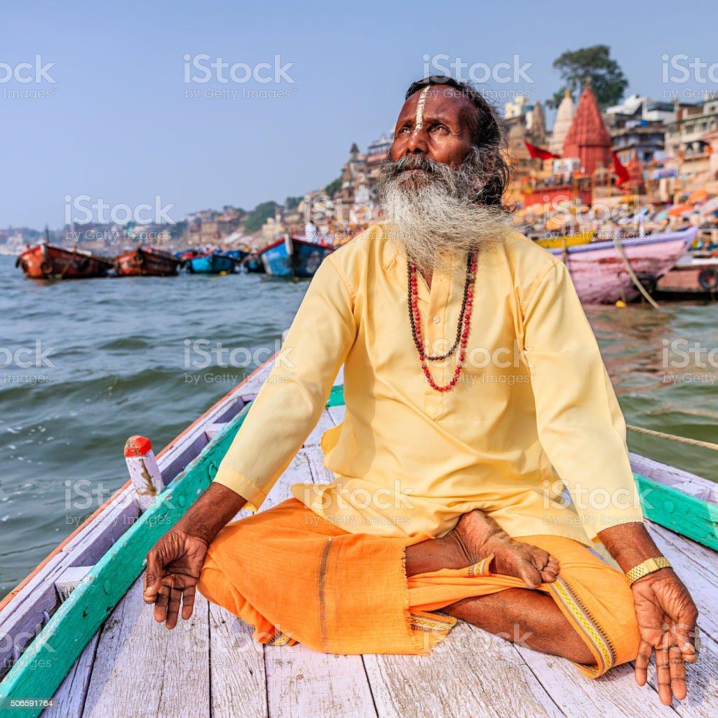 Sadhu is meditating in boat on Holy Ganges River, Varanasi stock photo