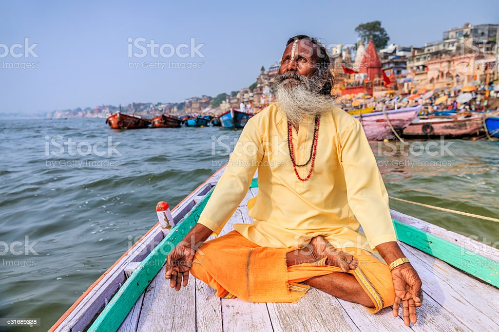 Sadhu is meditating in boat on Holy Ganges River, Varanasi stock photo
