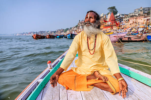 sadhu is meditating in boat on holy ganges river, varanasi - hinduism stock photos and pictures