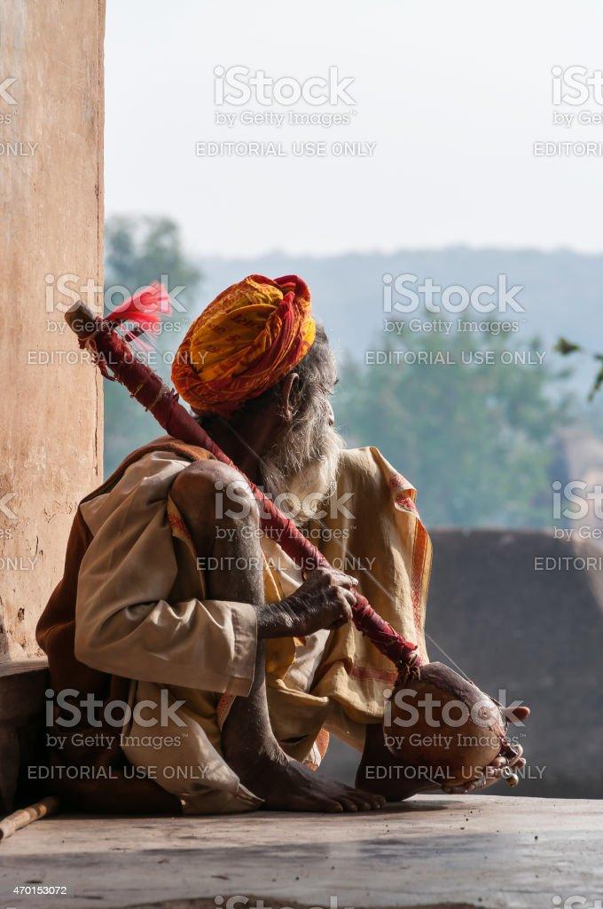 Sadhu sitting and playing the tumbi stock photo