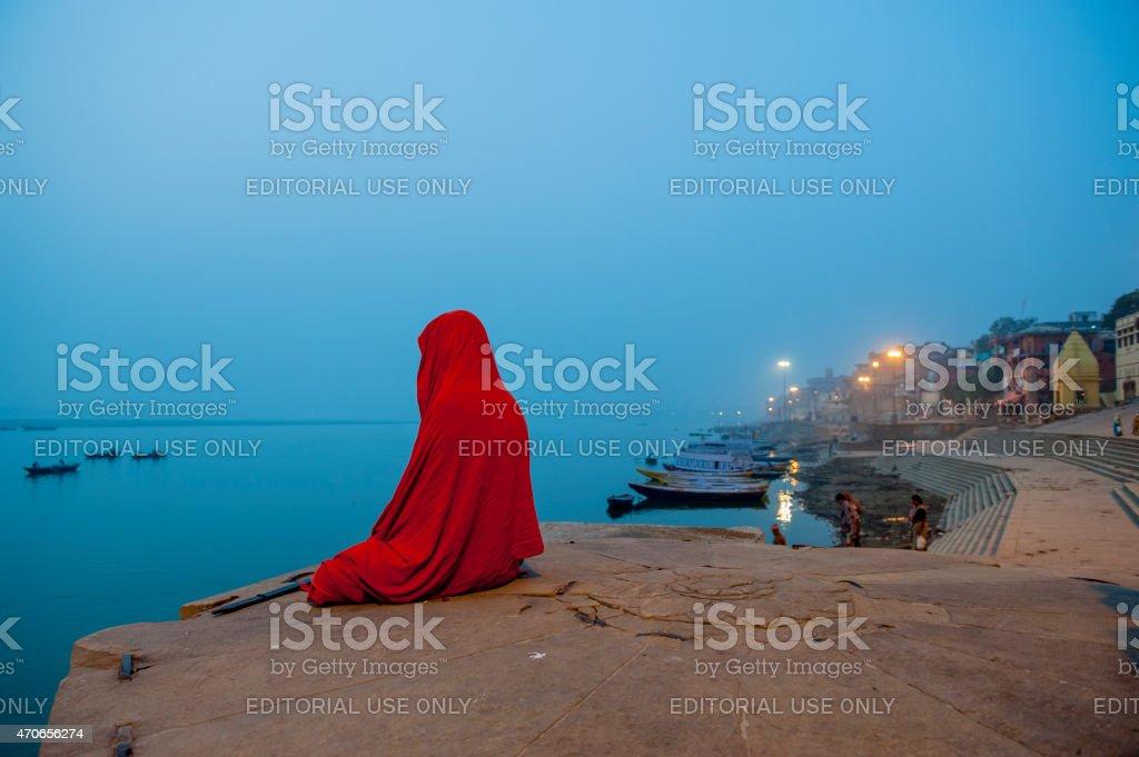Sadhu sitting on the bank of Ganges River meditating stock photo