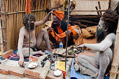 Kolkata, India - January 12, 2014: Unidentified Sadhus (Hindu Saints) relaxing in their temporary tent, in Babughat transit camp, Kolkata. They are on their way to Holy place Gangasagar (Sagar). Every year Hindu Sadus from all over India come to Gangasagar for their Holy bathe and stay at Babughat, Kolkata in transit.