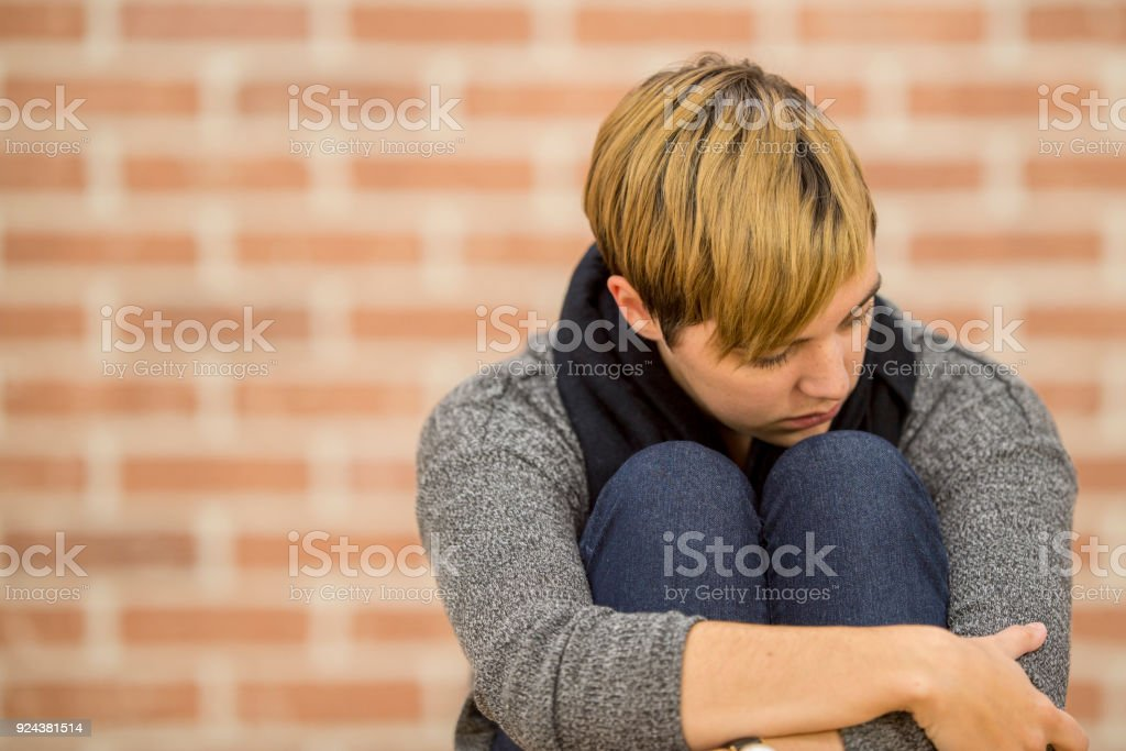 A Caucasian woman is sitting indoors in front of a brick wall. She is...