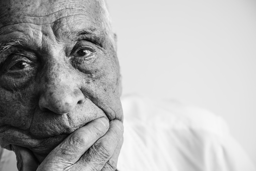 An old man looking at camera, covering his mouth with his hand. Black and white photo.