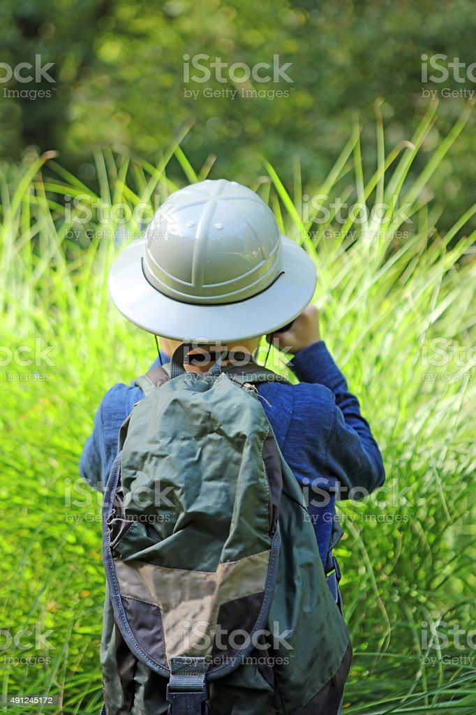 This is a rear view vertical image of a 7 year old boy who is wearing...