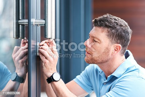 Shot of a handsome mature locksmith installing a lock