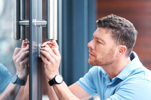Safe and secure Shot of a handsome mature locksmith installing a lock locksmith stock pictures, royalty-free photos & images