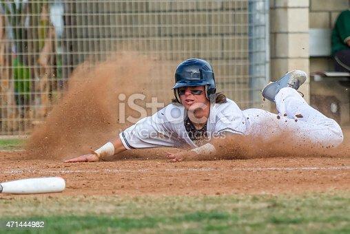 A baseball player slides head first into home scoring a run.