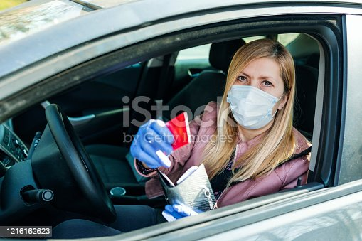 Woman in the car with protective glove and facial mask.Health protection.She gives  credit card through the cars window .