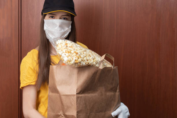 Safe Food Delivery and Online Orders. Young woman courier in uniform in a medical antibacterial mask and gloves stands at the door with a package stock photo