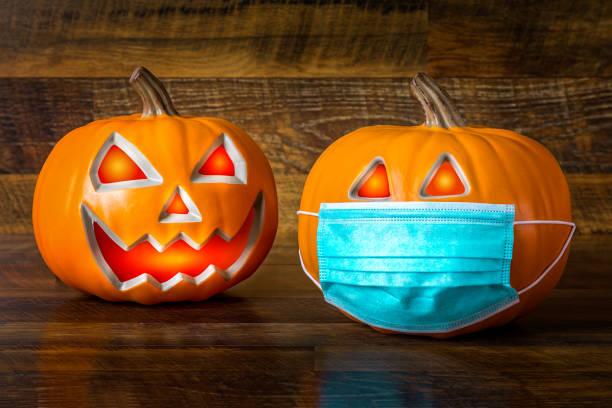 safe halloween 2020 durante el covid-19 pandemc. calabazas de halloween con máscara facial - halloween covid fotografías e imágenes de stock