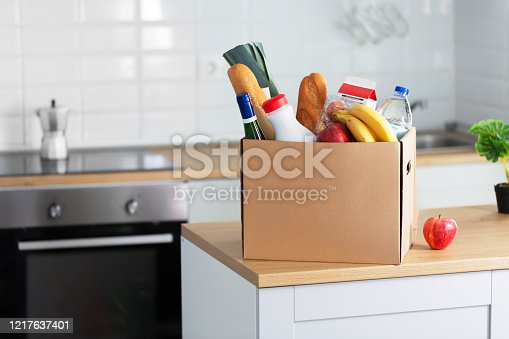 Safe home delivery. A box of different food such as milk, fruits and bread on the modern kitchen.