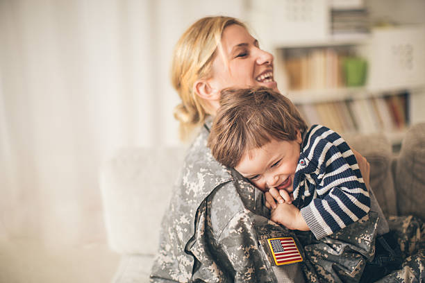 safe in mommy soldier's hug - armed forces stock photos and pictures