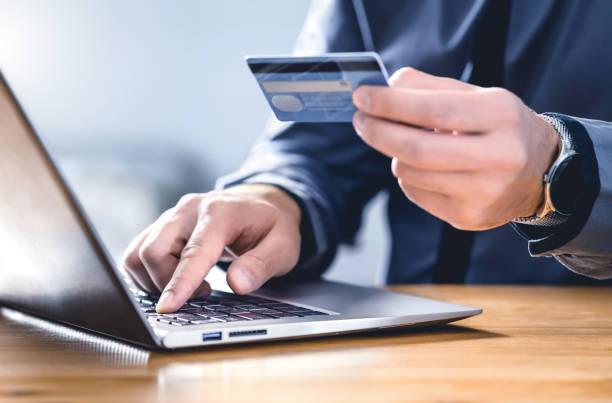 Safe online payment and electronic money transfer security. Pay with digital technology. Man using credit card and laptop to login to internet bank. stock photo