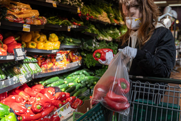 Sichere Einkaufspraxis während eines viralen Pandemieausbruchs. Eine junge Frau, die eine Schutzmaske und Handschuhe beim Gemüseeinkaufs in einem Geschäft trägt. – Foto
