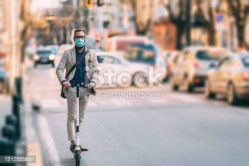 Businessman with mask riding scooter as alternative mode of transport in the city during COVID-19 pandemic