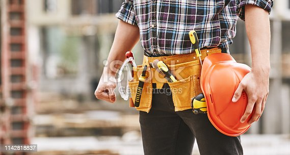 istock Safe work. Cropped photo of male professional builder with construction tools holding a safety red helmet while standing outdoor of construction site 1142818837