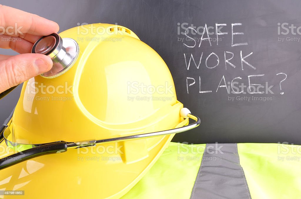 Safe work place handwritten in white chalk with a yellow hard hat and...