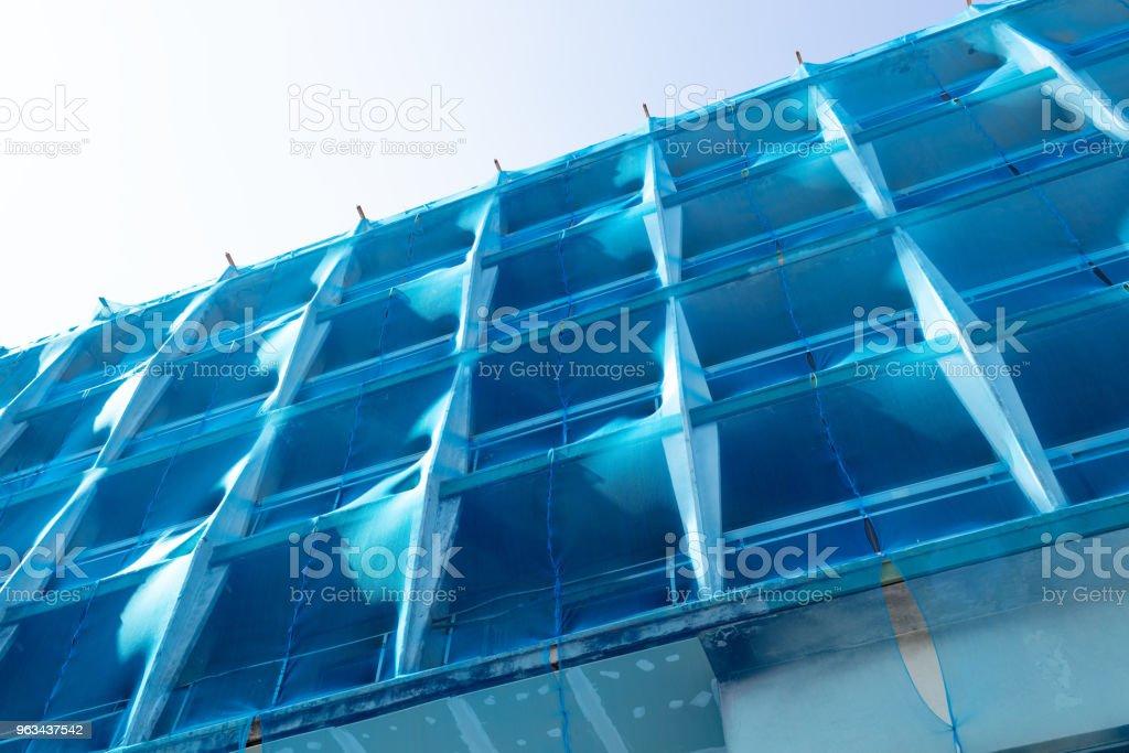 konstrukcja budynku z niebieską siatką bezpieczeństwa - Zbiór zdjęć royalty-free (Architektura)