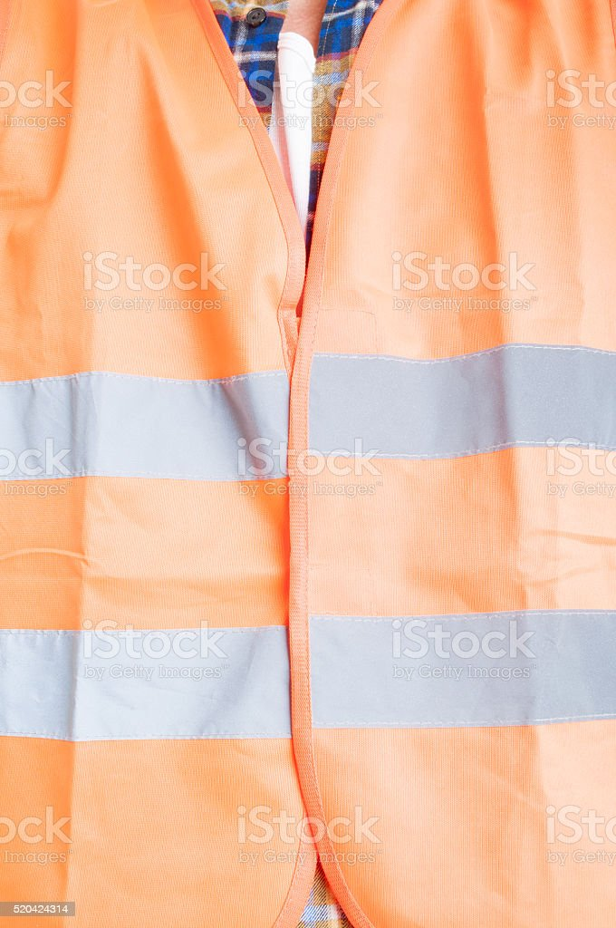 Safety construction concept with orange protection vest in close stock photo