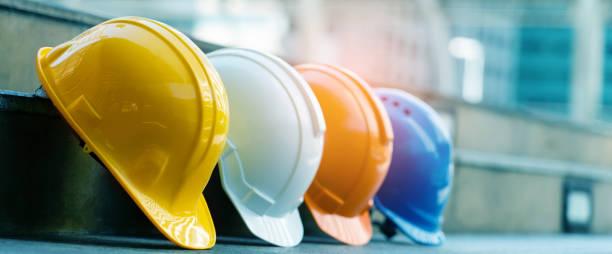 bezpieczeństwo budowlańca kapelusze niebieski, biały, żółty, pomarańczowy. praca zespołowa zespołu budowlanego musi mieć jakość. czy to inżynier, budowlańcy. mieć kask do noszenia w pracy. bezpieczeństwo w pracy. - kask ochronny odzież ochronna zdjęcia i obrazy z banku zdjęć