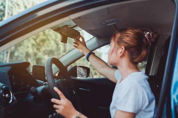 la mujer que conduce la seguridad ajusta el espejo retrovisor del coche en el interior antes de comenzar el viaje cada vez. - conducir fotografías e imágenes de stock
