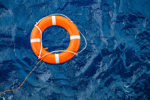 Safety equipment, Life buoy or rescue buoy floating on sea to rescue people from drowning man.