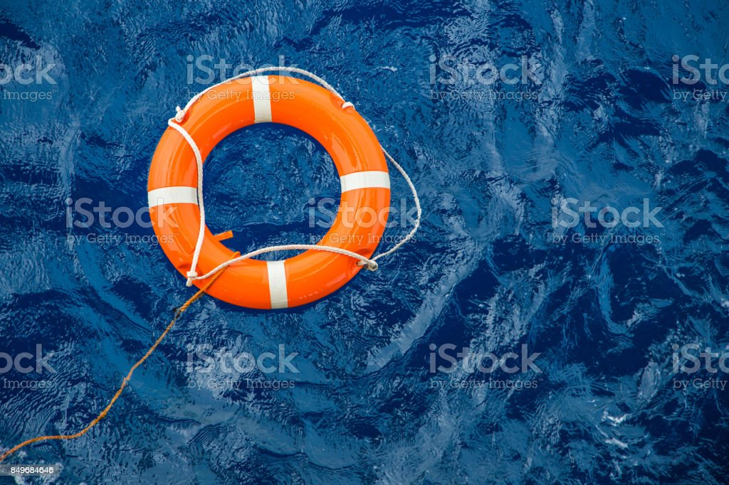 Safety equipment, Life buoy or rescue buoy floating on sea to rescue people from drowning man. stock photo