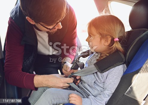 Safety first when your most valuable gift is on board! Father puts his daughter in her seat in the car and ties the seat belt. Nikon Z7