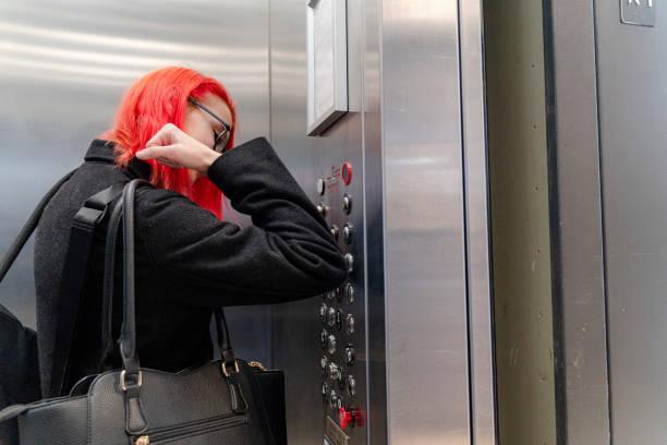 Sicherheit an erster Stelle. In Zeiten der Pandemie müssen Sie Vorsichtsmaßnahmen beim Umgang mit Aufzügen treffen, um eine Ausbreitung von Krankheiten zu verhindern. Teenager-Mädchen drücken Sie den Knopf mit ihrem Ellenbogen. – Foto