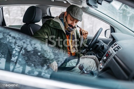 Mature man buckling her seatbelt in car