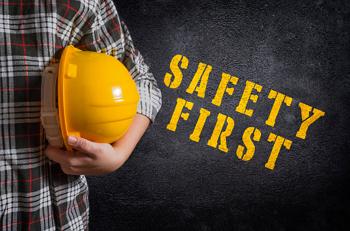 Safety first concept. Safety first stencil print on the black concrete wall. Construction worker with yellow safety helmet.