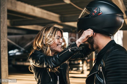 Attractive woman putting a biker helmet on the head.