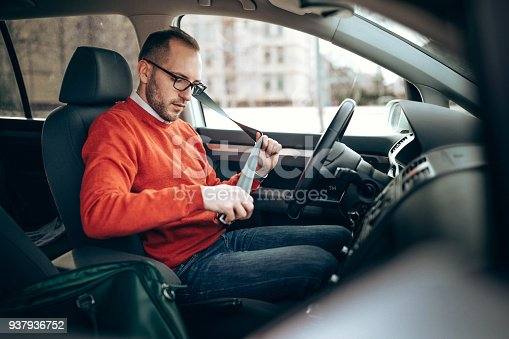 Photo of young man pulling seat belt in the car