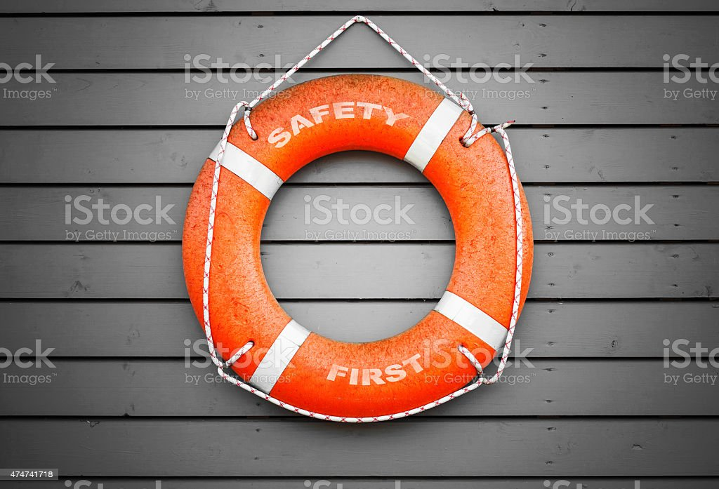Safety first. Red lifebuoy hanging on gray wall stock photo
