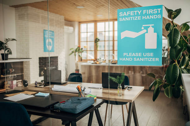 Safety first, sanitize hands sign on glass in in empty modern office