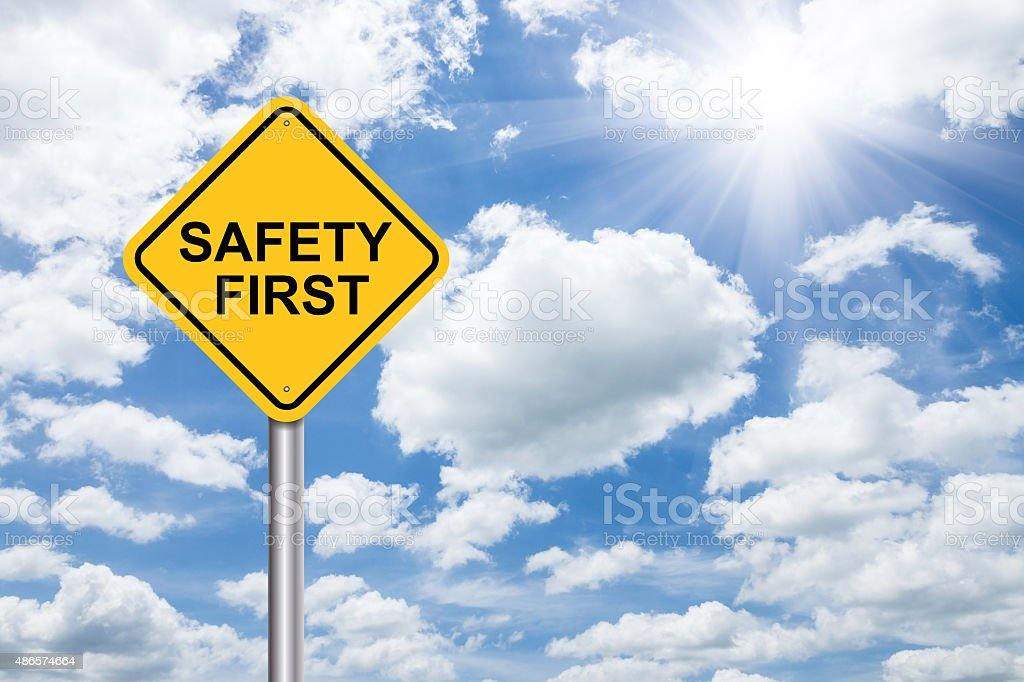 safety first sign on blue sky stock photo