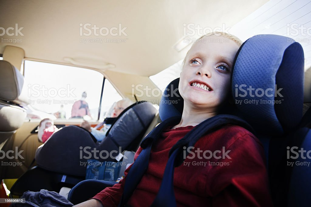 Safety first! Two kids secured in car seats and restraints stock photo