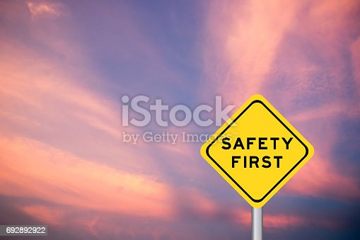 istock Safety first wording on yellow transportation sign with violet cloud sky background 692892922