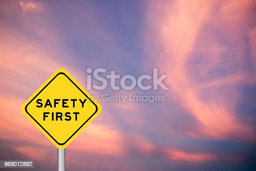 istock Safety first wording on yellow transportation sign with violet cloud sky background 869012892