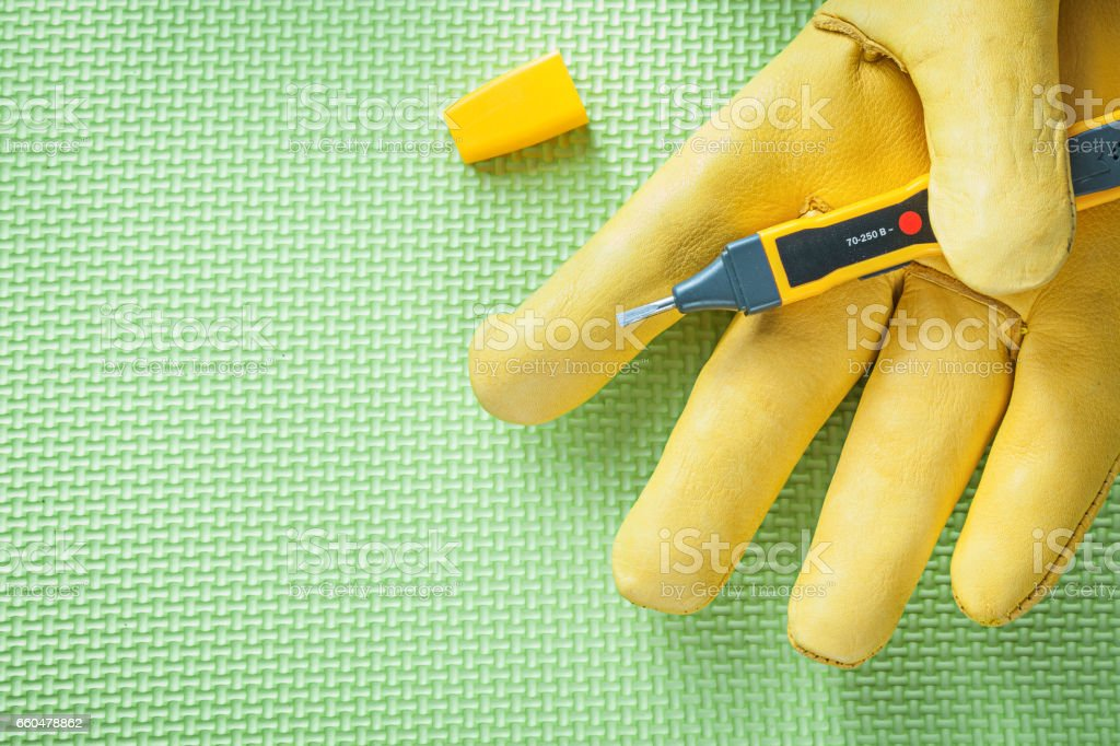 Safety glove electric tester on green background electricity con stock photo