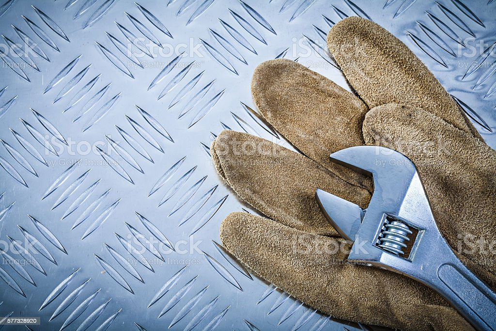 Safety gloves adjustable wrench on grooved metal plate construction...