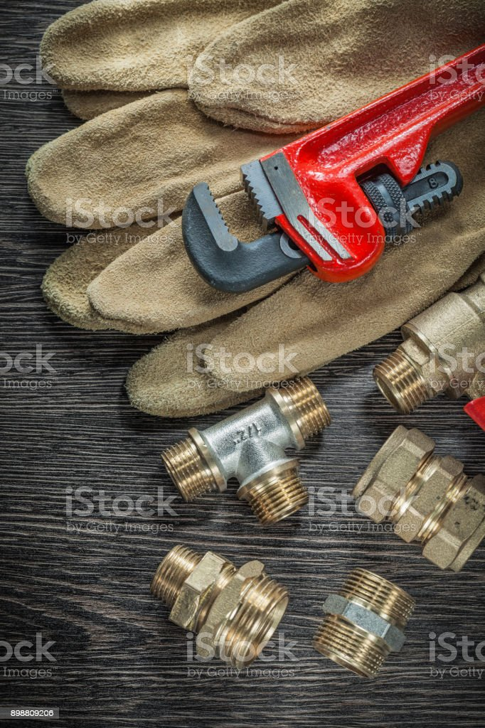 Safety gloves plumbing pipe wrench fittings water valve on woode stock photo