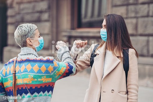 Two women with protective masks touching elbows outdoors in the city
