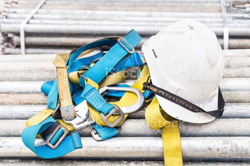 Safety harness and helmet at construction site stock photo