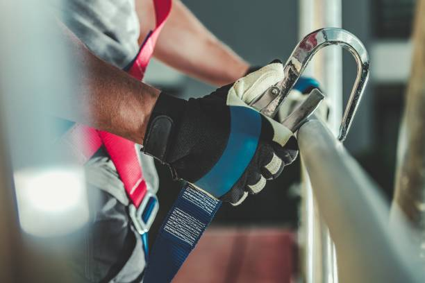 Safety Harness Hook Attaching Safety Harness Hook Attaching to Scaffolding by Construction Worker. safety harness stock pictures, royalty-free photos & images