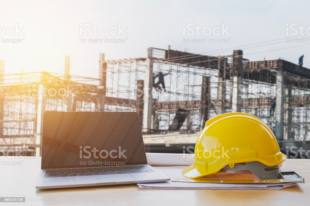 safety helmet and computer laptop on table in concstruction site royalty-free stock photo