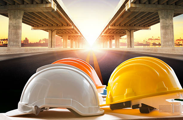 safety helmet on civil engineering working table against bridge - civil engineering stock pictures, royalty-free photos & images