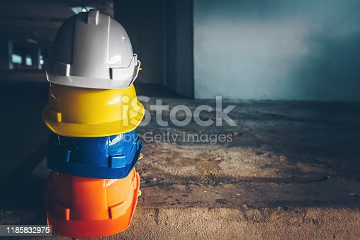 Safety helmet, white, yellow, blue and orange, placed on the cement floor in the construction site.
